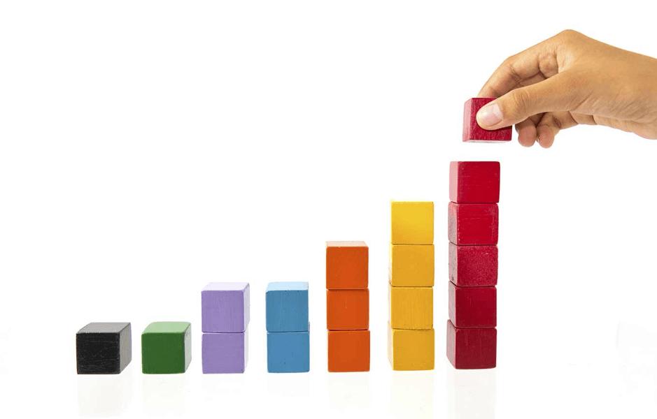 a hand assembling building blocks